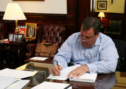 Christie-at-desk-signing-budget